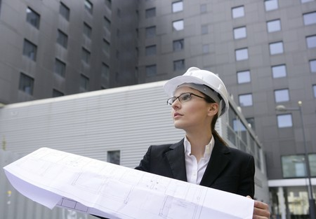 executive helmet: architect woman working outdoor with modern buildings
