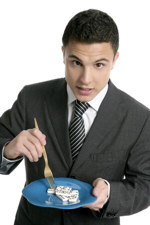 Businessman eating domino risk meatphor,  blue dish gold fork photo