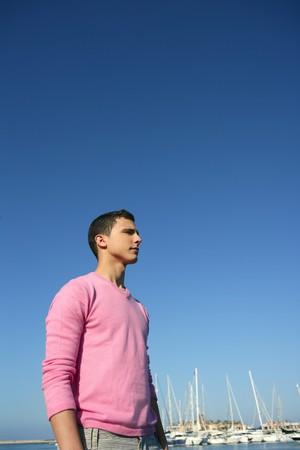 Handsome young man on summer in harbor, blue sky photo