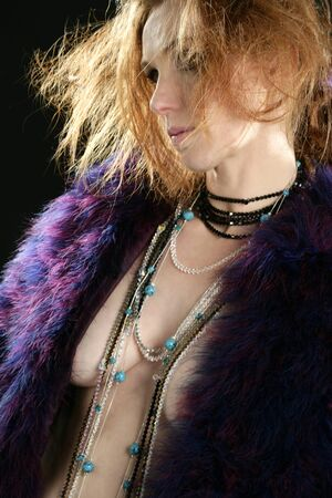 Beautiful sexy redhead woman with feather coat and jewelry, over black photo