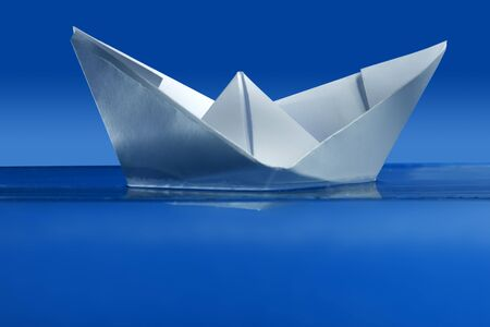 Paper boat floating over blue real water, side view Stock Photo