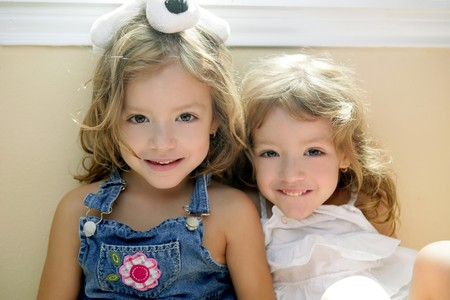 Two little beautiful toddler twin sisters portrait