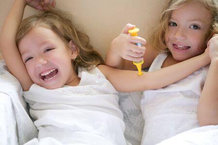 fake smile: Two little twin sisters playing to be doctors with syringe Stock Photo
