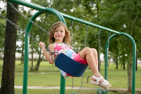 Beautiful little blond girl playing with swing at the green park