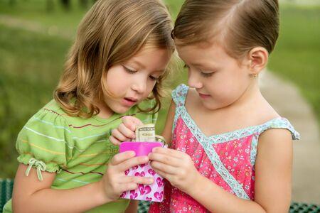 soeur jumelle: Deux petites filles de trouver un dollar note dans un petite bo�te rose Banque d'images