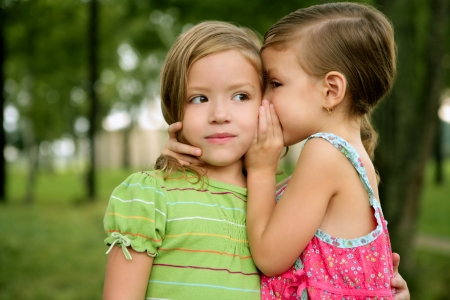 Two twin little sister girls whisper in the ear, outdoor on green park photo