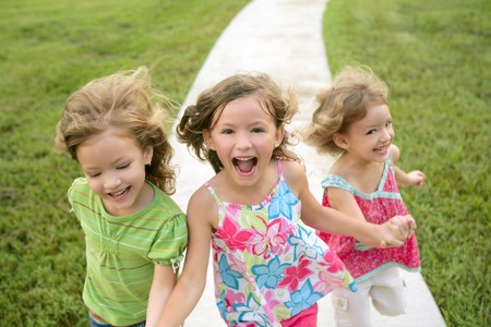 kid's day: Three sister girls playing running on the green park outdoor Stock Photo