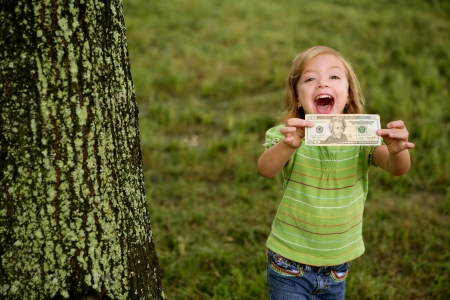 money in hand: Beautifull happy little girl with dollar noteon her hands Stock Photo