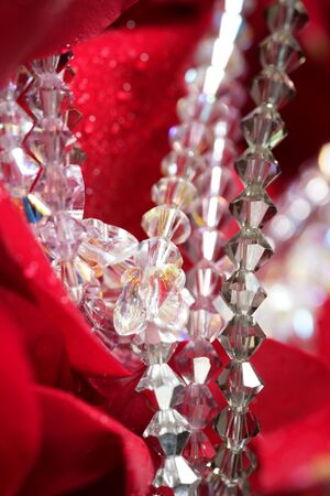 Shiny jewelry over bed or red rose petals photo