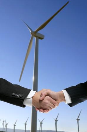 Businessmen handshake environmental agreement over wind mills photo