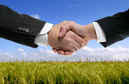 Businessman teamwork partners shaking hands in green nature Stock Photo