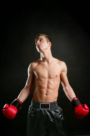 Boxer, young age handsome man over black background photo