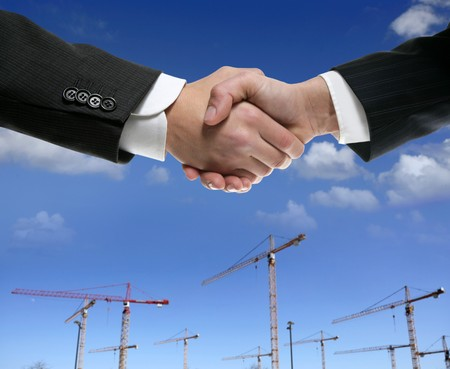 men shaking hands: Businessmn handshake in construction crane area over blue sky Stock Photo
