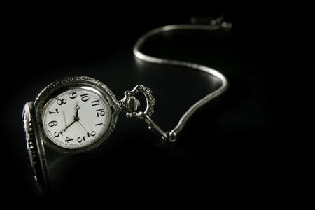 old vintage antique pocket clock, silver watch over black photo