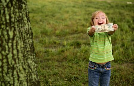 hands holding tree: Beautifull happy little girl with dollar noteon her hands Stock Photo