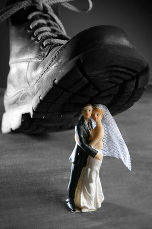 the end: Tread a marriage couple figurine with a big old boot, divorce metaphor Stock Photo