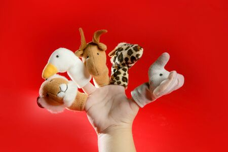 Finger puppets on a toddler hand over red background Stock Photo - 4516264