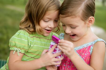 Two little twin sisters playing with pink box outdoor Stock Photo