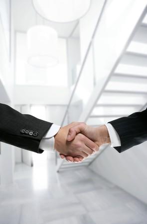Businessman handshake on modern white stairway office