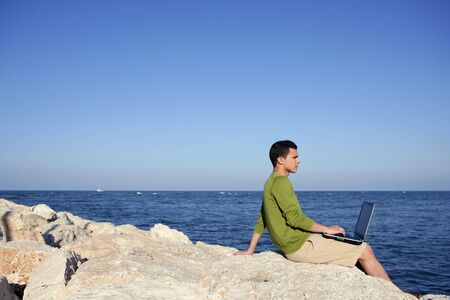 Handsome young businessman with computer on the blue ocean beach