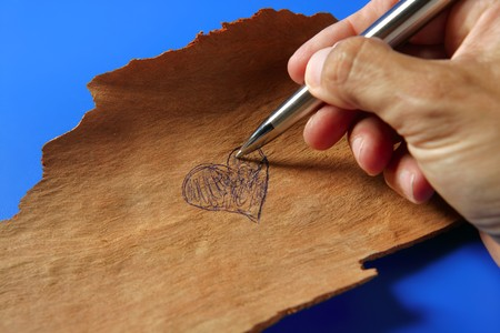 Human hand writing, drawing with a pen a heart on wood, valentines day photo