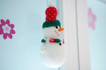 Little toy snowman hanging on the white window, girl room photo