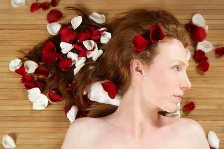 Redhead beautiful woman with colorful rose petals on hair photo