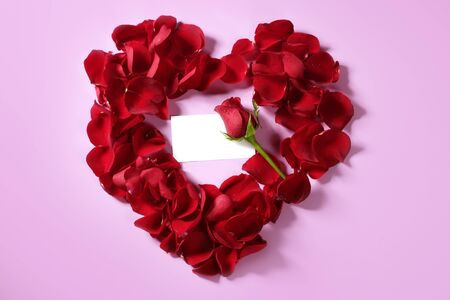 Red rose petals in heart shape with a copy space blank note Stock Photo - 4575079