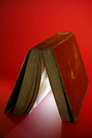 within: Old aged book close up, light glowing inside, over red background
