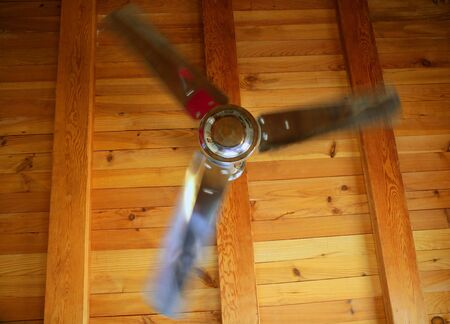 Silver ceiling fan on a golden wooden beams background, summer metaphor photo