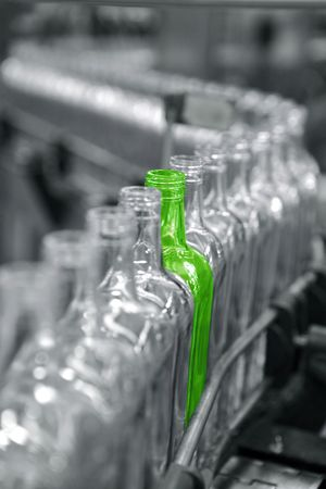 factory line: Bottles in a factory line, one different unique green Stock Photo
