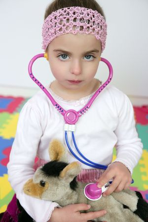 Beautiful preschooler girl pretending to be an animal doctor, stethoscope photo