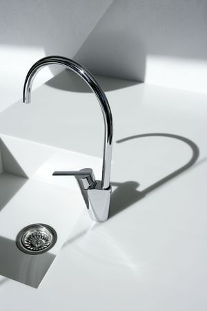 White modern kitchen detail, faucet and sink with shadows