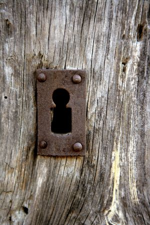 Key hole over aged gray old wood, rusty metal photo