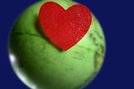 Red candy valentines heart over the world green global earth map photo