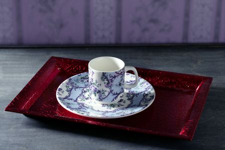 Tea cup victorian style on red indian tray, purple wallpaper background  photo