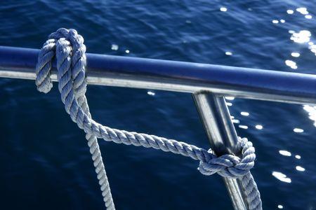 Nautical marine fender knot around stainless steel lee on blue ocean sea photo