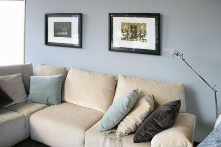 Living room with cream sofa, soft blue wall, interior design