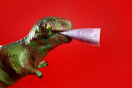Toy dinosaur with euro note in its yaws over red background photo
