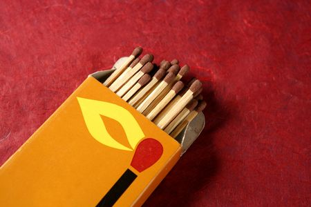 Wooden matches in a box over red background photo