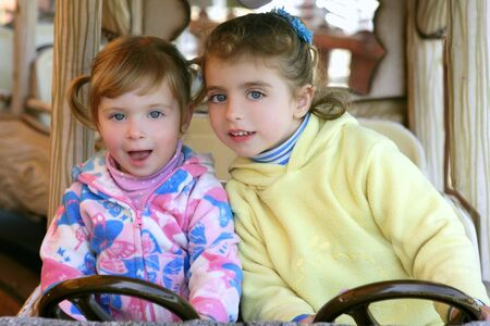 Two beautiful sister little girls driving car on winter fairground photo