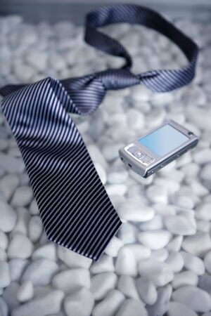 Businessman on a break, left his tie and phone on a modern white stones table Stock Photo - 4634928
