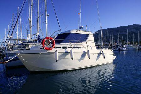 Sport fishing vacation boat on Mediterranean marina on blue water photo
