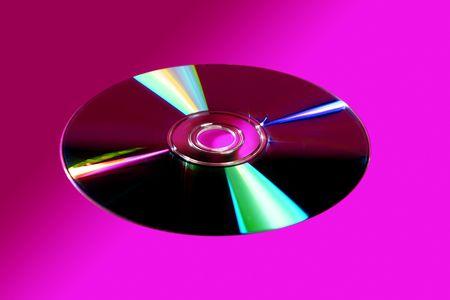 reflexion: De CD de disco DVD con la reflexi�n de colores sobre fondo de color rosa fuerte Foto de archivo