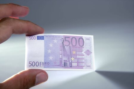 Human fingers holding little euro notes currency over gray background photo