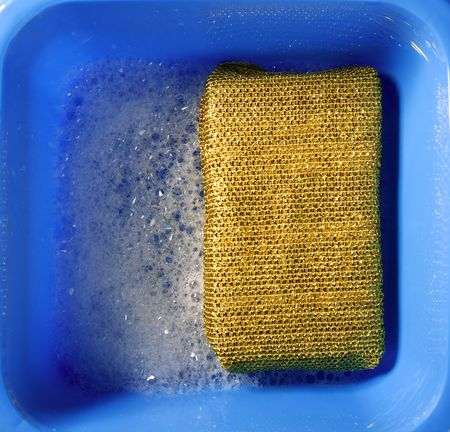 Cleaning housewife stuff, golden sponge on blue square pail, white foam photo
