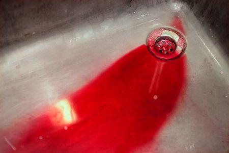 killer cells: Blood in vivid red in a stainless steel sink, murder metaphor Stock Photo