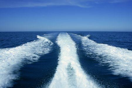 Fishing speedy boat prop wash, white wake on the blue ocean sea