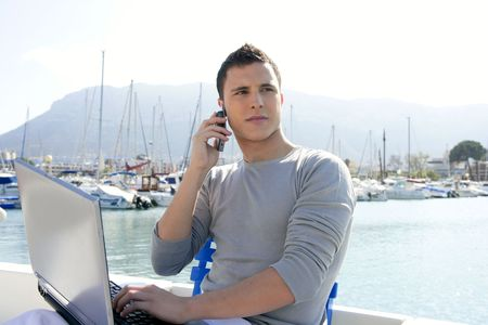Businessman working with computer on a boat, nice outdoor office photo
