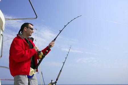 Fisherman fishing on boat big game tuna, blue sunny sky Stock Photo